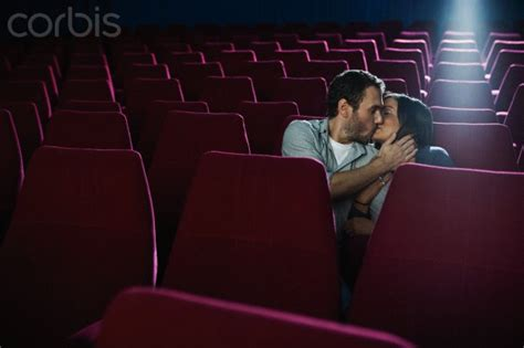 Couple kissing in an empty movie theatre - 42-25979689